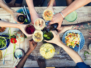 People surrounding table with food and cheersing