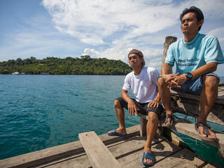 Yusef Bural and his brother on a dock in the ocean