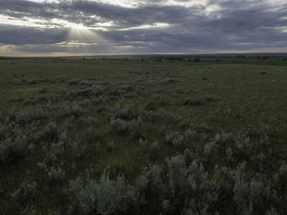 The sun shines through clouds on the plains