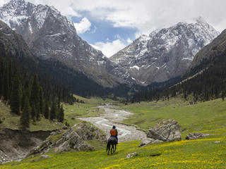 A horseback rider rides through the mountains