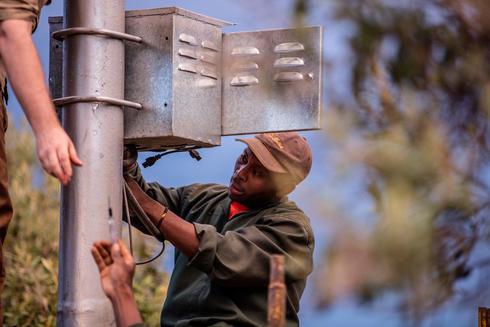 A man installing solar panels for FLIR camera system