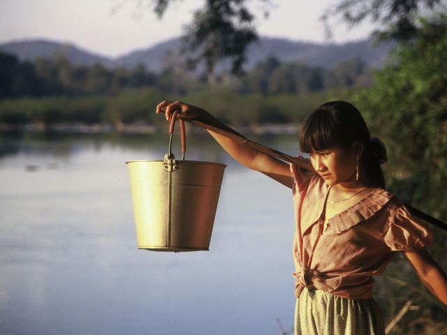 Tribal girl collects water in the evening from the Serepok River in a poor commune in Vietnam's Central Highlands where thousands of poor villagers have access to sanitation