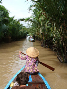 Local woman rowing a boat on a branch of the Mekong river
