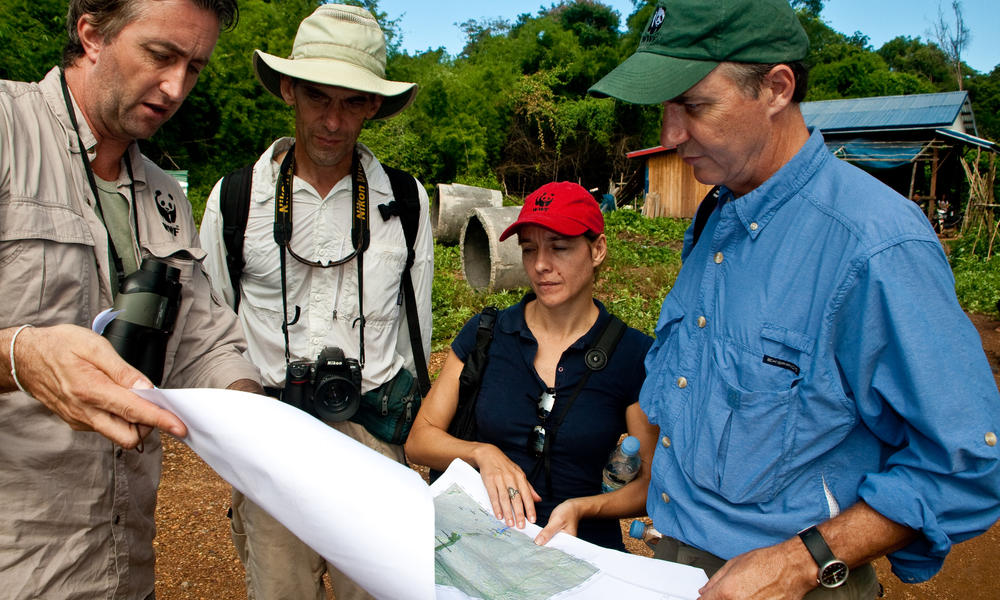 WWF staff reviewing a map of the Mekong River Basin. From left to right: Stuart Chapman, Interim Representative for WWFs Greater Mekong Program; Gordon Congdon, Freshwater Coordinator, WWF-Cambodia; Michelle Owen, Country Director, WWF-Cambodia; Carter R