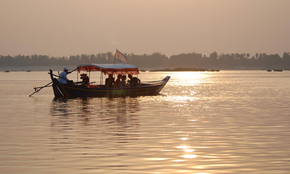 Tourists cruise along the Mekong in search of the charismatic, but highly threatened Irrawaddy dolphin.