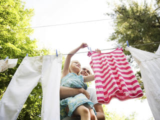 Father and daughter hang laundry outside