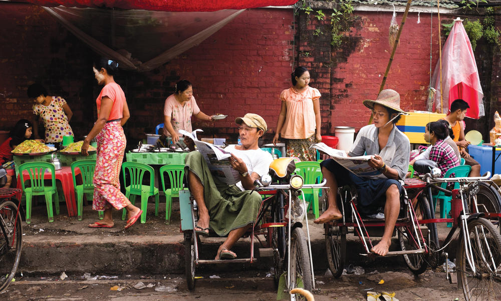 Locals eat, drink, talk—and take in the news—at a streetside teashop on Pansodan Jetty in downtown Yangon.