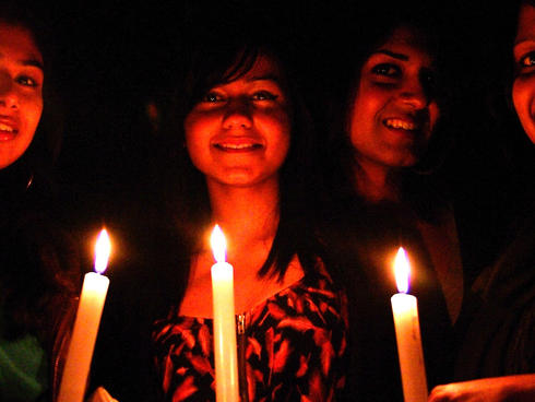Revellers with candles celebrate Earth Hour at Dunedin's Octagon community event, South Island, New Zealand.