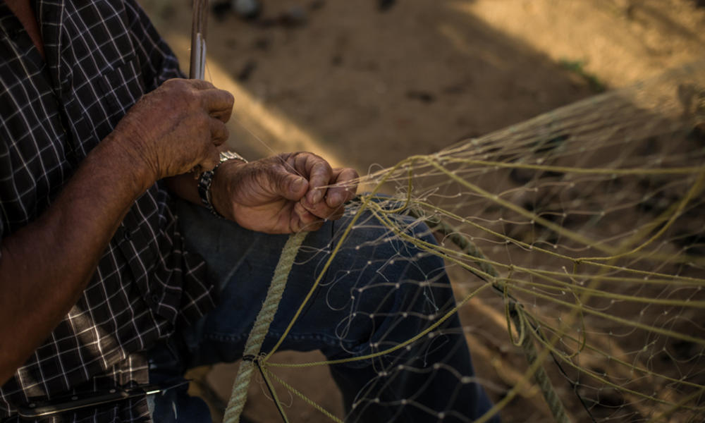 Luis Sanhueza, 73, mends a fishing net in Cocholgue, a small fishing village near Concepcion, Chile.