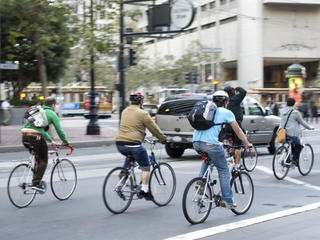 Commuters bike to work in city Environmentally conscious bikers cycling in traffic in San Francisco, California, United States