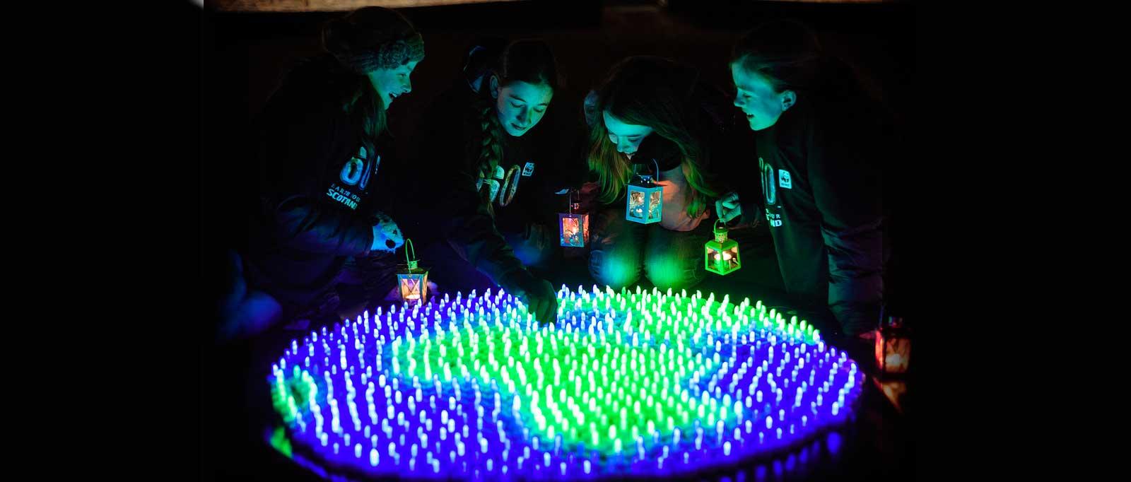 Participants surround glow in the dark globe